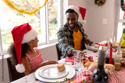 Happy african american father and daughter talking at christmas table