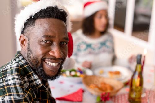 Happy african american man looking at camera at christmas table