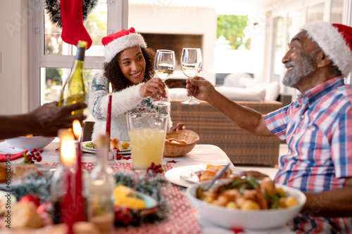 Happy african american adult daughter and her senior father making toast at christmas table