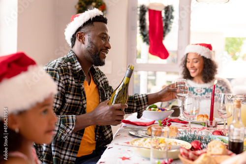Happy african american father pouring wine to glass at christmas table