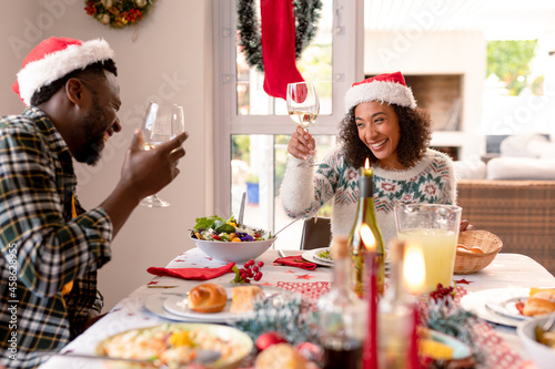 Happy african american couple making toast at christmas table