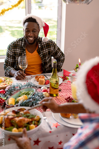 Happy african american man wearing santa hat holding glass at christmas table