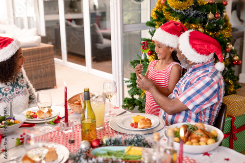 Happy african american mother, daughter and grandfather in santa hats talking at christmas table