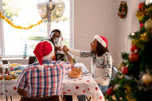 Happy multi generation family wearing santa hats, toasting with vine, having christmas meal