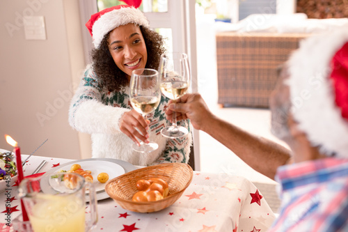Happy african american adult daughter and senior father making toast at christmas table