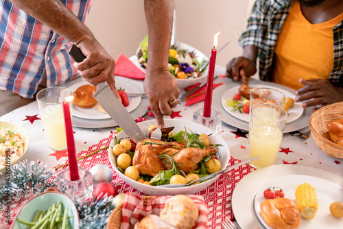 Hands of african american man cutting chicken at christmas meal