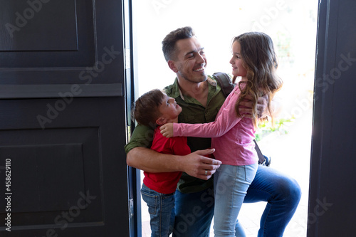 Happy caucasian siblings welcoming father returning home after work