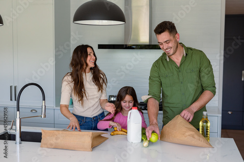 Happy caucasian parents and daughter unpacking groceries in kitchen