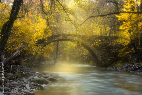 Canvas Scenic view of a creek flowing downstream with autumnal trees and an old bridge
