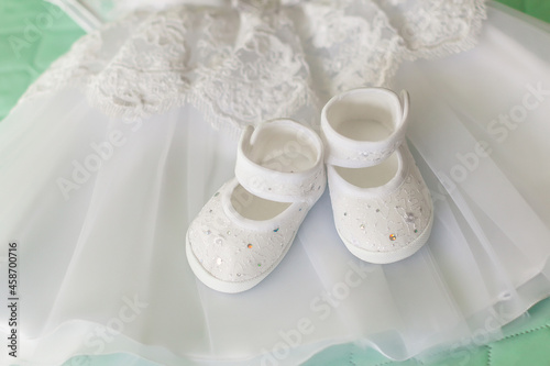 Foto White baby shoes on a white dress for christening