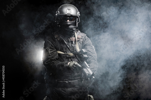 Canvastavla Professional special forces fighter in a helmet and with special weapons shrouded in smoke on a black background