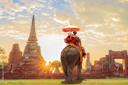 Fototapeta Tourists lover on an ride elephant tour of the ancient city sunset ,ayutthaya, t