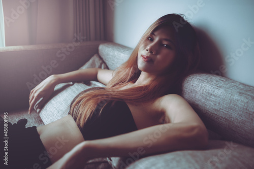 Canvas Print Sporty Asian woman is posing cool on sofa with seductive active black clothing for Street Girl fashion style