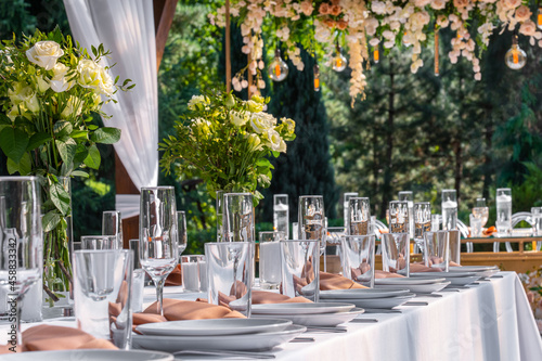 Fototapeta Wedding table setting decorated with fresh flowers in a brass vase