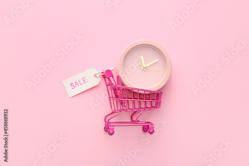 Fototapeta Alarm clock in small shopping cart on pink background, top view