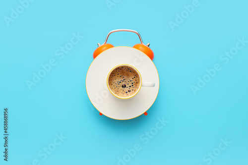 Fotografija Creative alarm clock made with cup of coffee on blue background