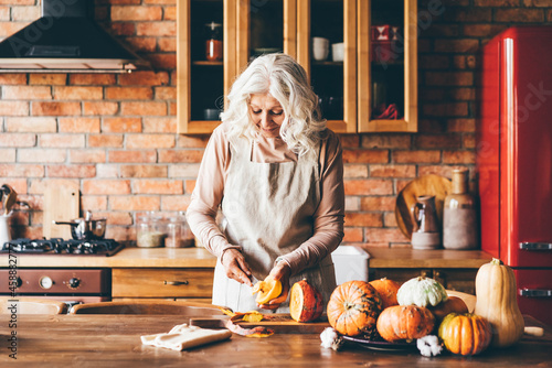 Fotografia Aged lady with long loose grey hair with knife chopping pumpkin on cutting board