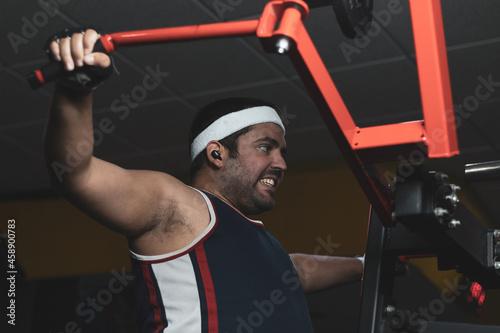 a funny fat boy doing sports inside a gym Fototapet