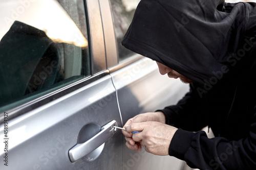 Photo Unrecognizable Car thief steal car breaking door criminal job burglar Hijacks Auto thief is trying break into automobile using tools