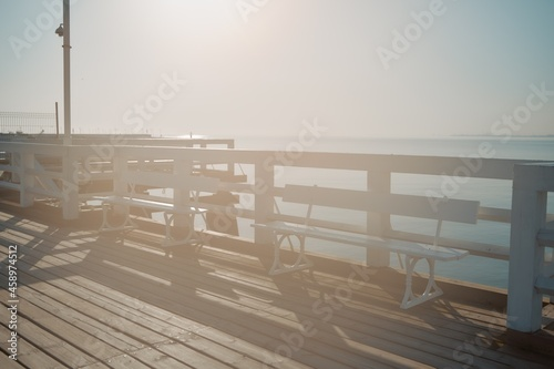 Fotografiet Hazed photo of the wooden pier with white painted handrails and bench