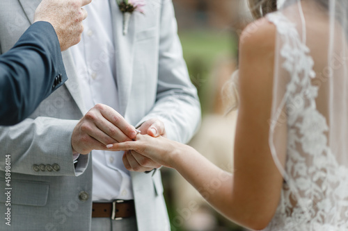 Fotografering Close up of groom putting a golden ring on the bride's finger cropped view of a