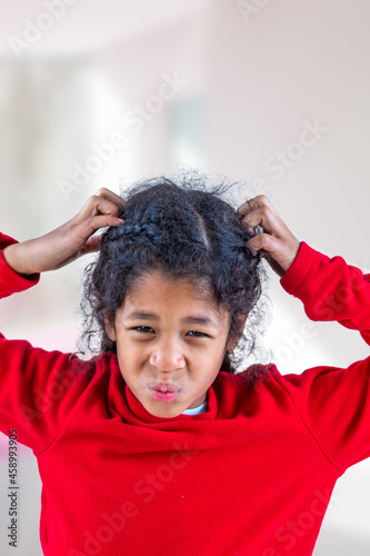 Fototapeta Girl itchy his hair on isolated indoors background health care.