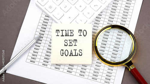 TIME TO SET GOALS text on sticker on the chart ,with calculator and magnifier