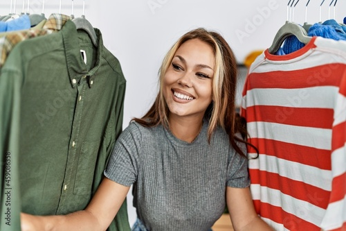 Canvas Print Young caucasian customer woman smiling happy appearing through clothes at clothing store