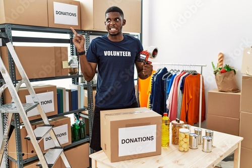 Fotografia, Obraz Young african american volunteer man packing donations box for charity pointing