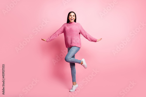 Full body portrait of cheerful pretty lady dance hands sides flying raise knee isolated on pink color background