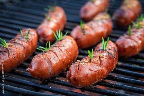 Billede på lærred Spicy sausage on grill with spices. Grill in garden.
