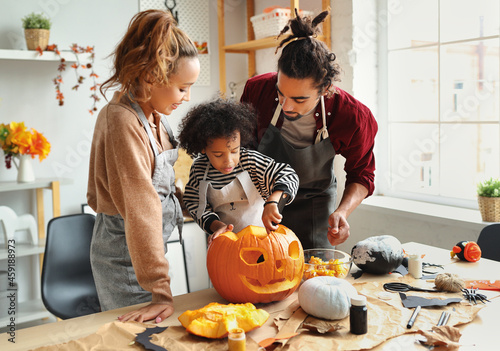 Canvas Print Happy african american family mother, father and child son carving pumpkin for H
