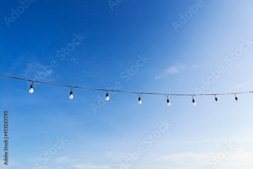 Canvastavla Beautiful clear sky with light bulbs hanging on a rope in park at Krabi Thailand and soft clouds make you feel and see the good weather in the morning of a new day