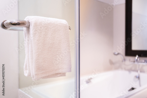 Fotografiet Sanitized white towel hanging on the shower room hand rail close upใ