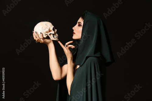 Fotografie, Obraz Young witch with human skull on dark background