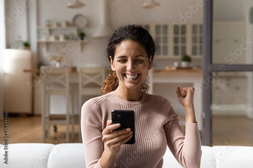 Fotografiet Overjoyed young Caucasian woman feel euphoric with online lottery win or victory on smartphone