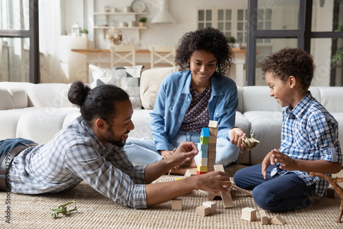 Fototapeta Happy African American parents and little son playing with construction toys, co