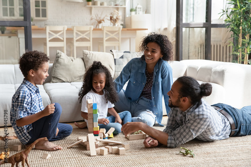 Fotografie, Obraz Happy African American parents and kids playing with construction toys together,