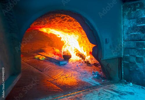 Fotografie, Obraz Traditional brick pita oven, burning wood and flames