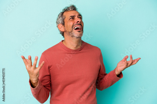 Murais de parede Middle age caucasian man isolated on blue background  screaming to the sky, looking up, frustrated
