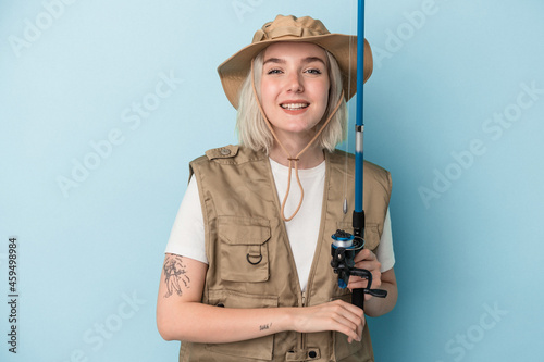 Obraz na plátně Young caucasian fisherwoman holding a rod isolated on blue background laughing and having fun