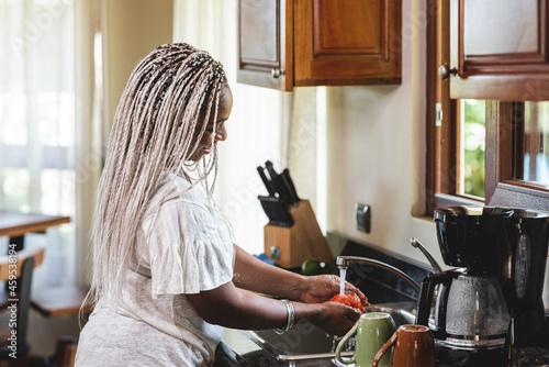 Wallpaper Mural mujer afroamericana en la cocina lavando las verduras