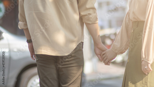 Obraz na plátně Young Asian couple holding each other's hands on the aisle It is a symbol of love, friendship and compassion