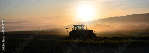 Fotografie, Obraz Tractor ploughing the field at sunrise in late summer or autumn.