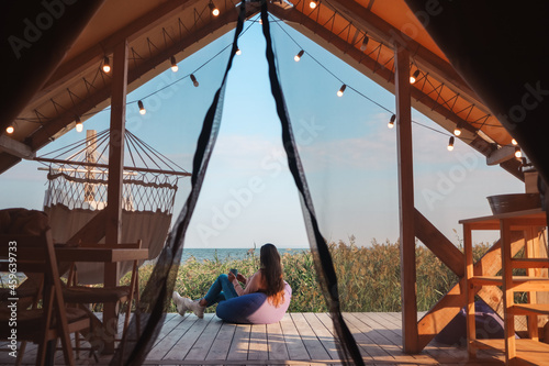 Beautiful young girl in nature by the lake. woman resting in glamping in a picturesque place far from the city. self-isolation leave without people