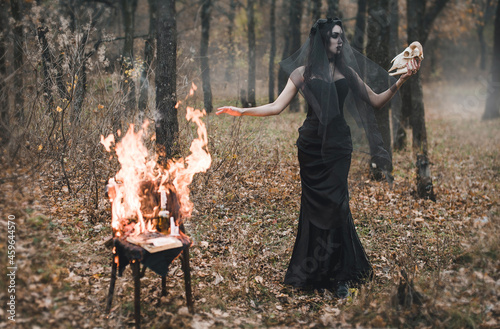 Obraz na płótnie Brunette witch girl conjures in the forest conducts rituals with a fantasy skull