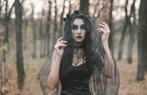 Canvas Print Brunette witch girl conjures in the forest conducts rituals with a fantasy skull