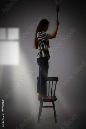 Slika na platnu Depressed woman with rope noose standing on chair in room