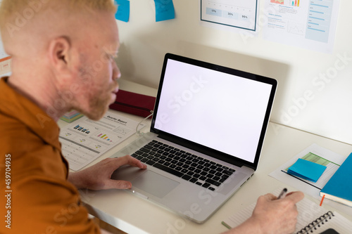 Albino african american man working from home using laptop with copy space