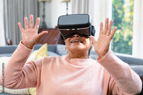 Happy mixed race senior woman wearing vr headset and having fun